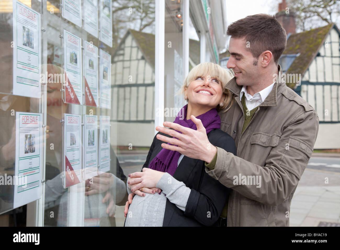 Giovane cercando in agenti immobiliari finestra Immagini Stock