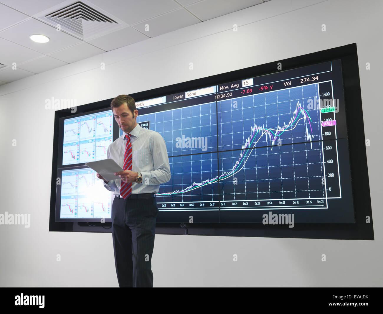 Imprenditore con il grafico su schermo Immagini Stock