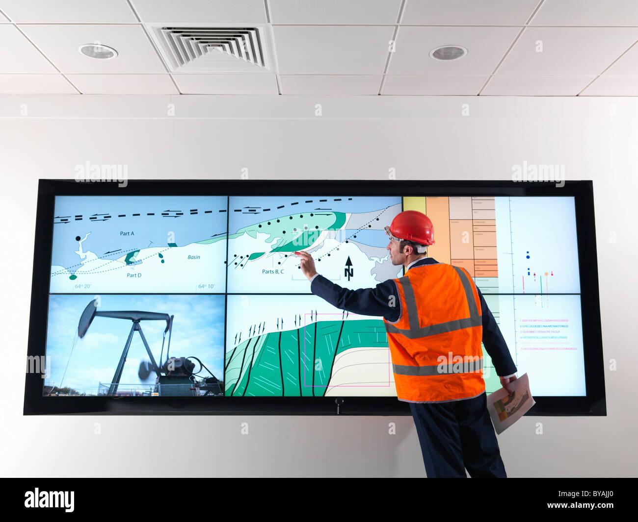 Lavoratore di olio con schermo di geologia Immagini Stock