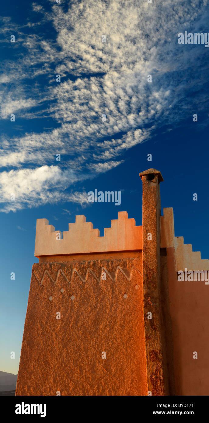 Texture e pattern di berber pise architettura con camino e puffy nuvole a sunrise tinerhir in Marocco Immagini Stock