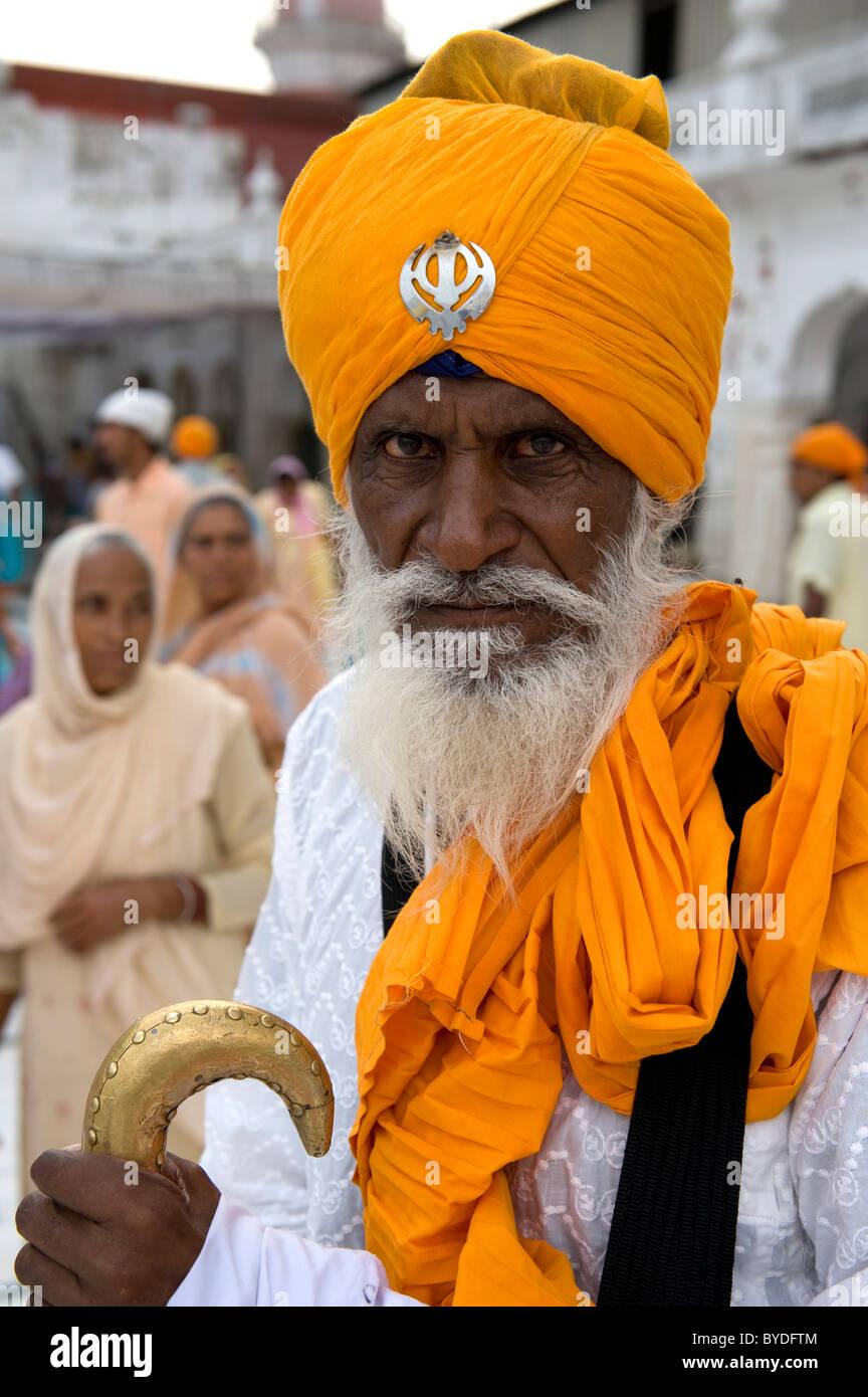 Il sikhismo, credente della religione Sikh con un turban arancione e Khanda simbolo sacro tempio d'oro, Hari Immagini Stock