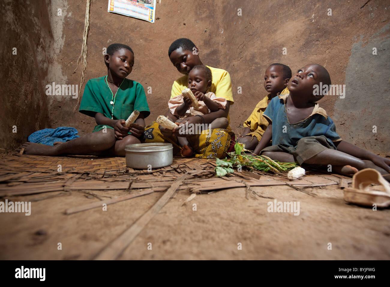 Una famiglia condivide un pasto insieme nella loro casa di fango in Masaka, Uganda, Africa orientale. Immagini Stock