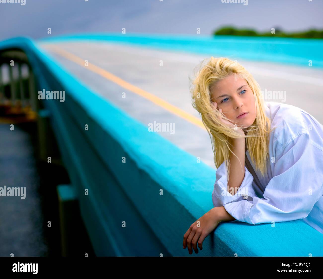 Giovane donna bionda sul ponte fantasticando Immagini Stock