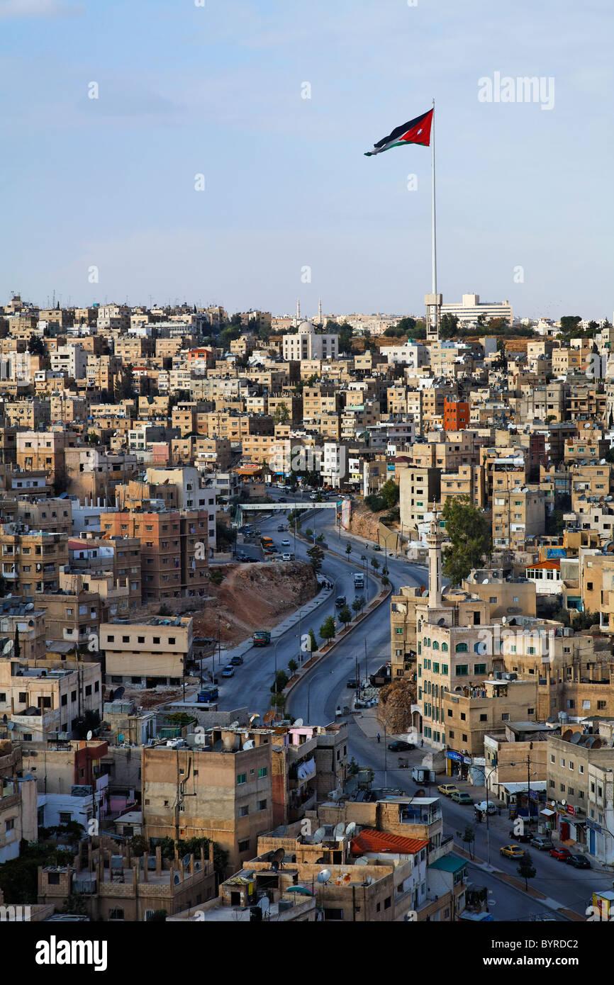 Grande bandiera giordana volando sopra la città di Amman in Giordania Immagini Stock