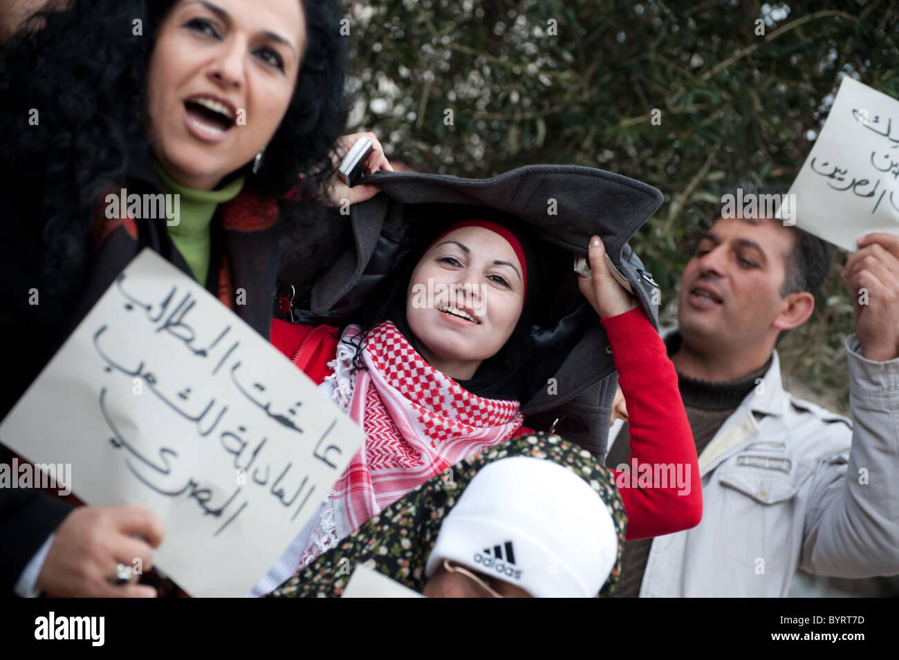 Un gruppo di attivisti palestinesi contiene i segni e i canti di slogan in solidarietà con proteste contro Immagini Stock