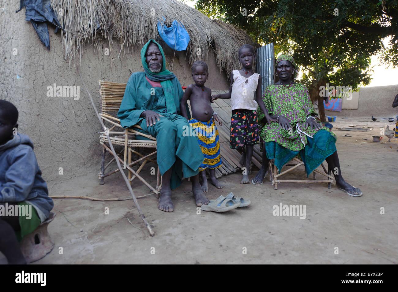 Grand genitori e grand bambini posa davanti la loro casa in un villaggio nel Niger Inland Delta. Mali. Immagini Stock