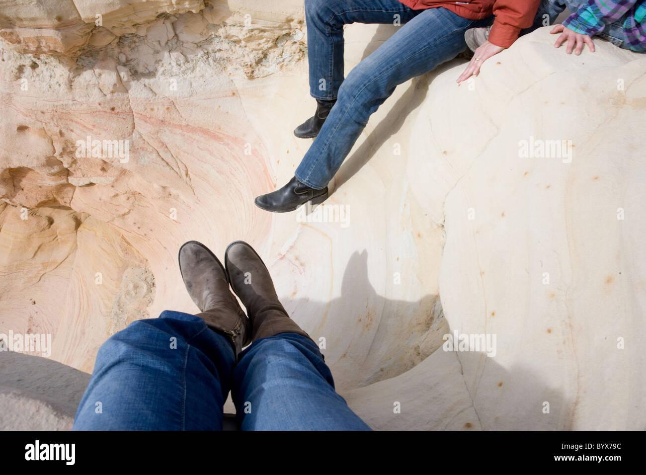 Donne che indossano stivali in appoggio sulla pietra arenaria, alto deserto del Nuovo Messico, STATI UNITI D'AMERICA Immagini Stock
