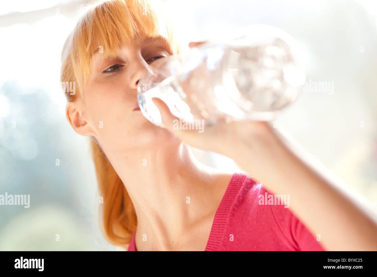 Donna di bere acqua in bottiglia Immagini Stock