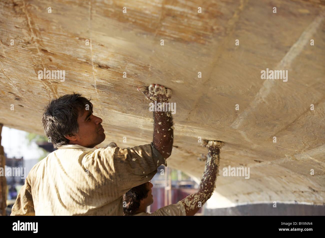 Due lavoratori applicare un sigillante al lato inferiore di una dhow nel cantiere Jaddaf, Dubai, UAE Immagini Stock