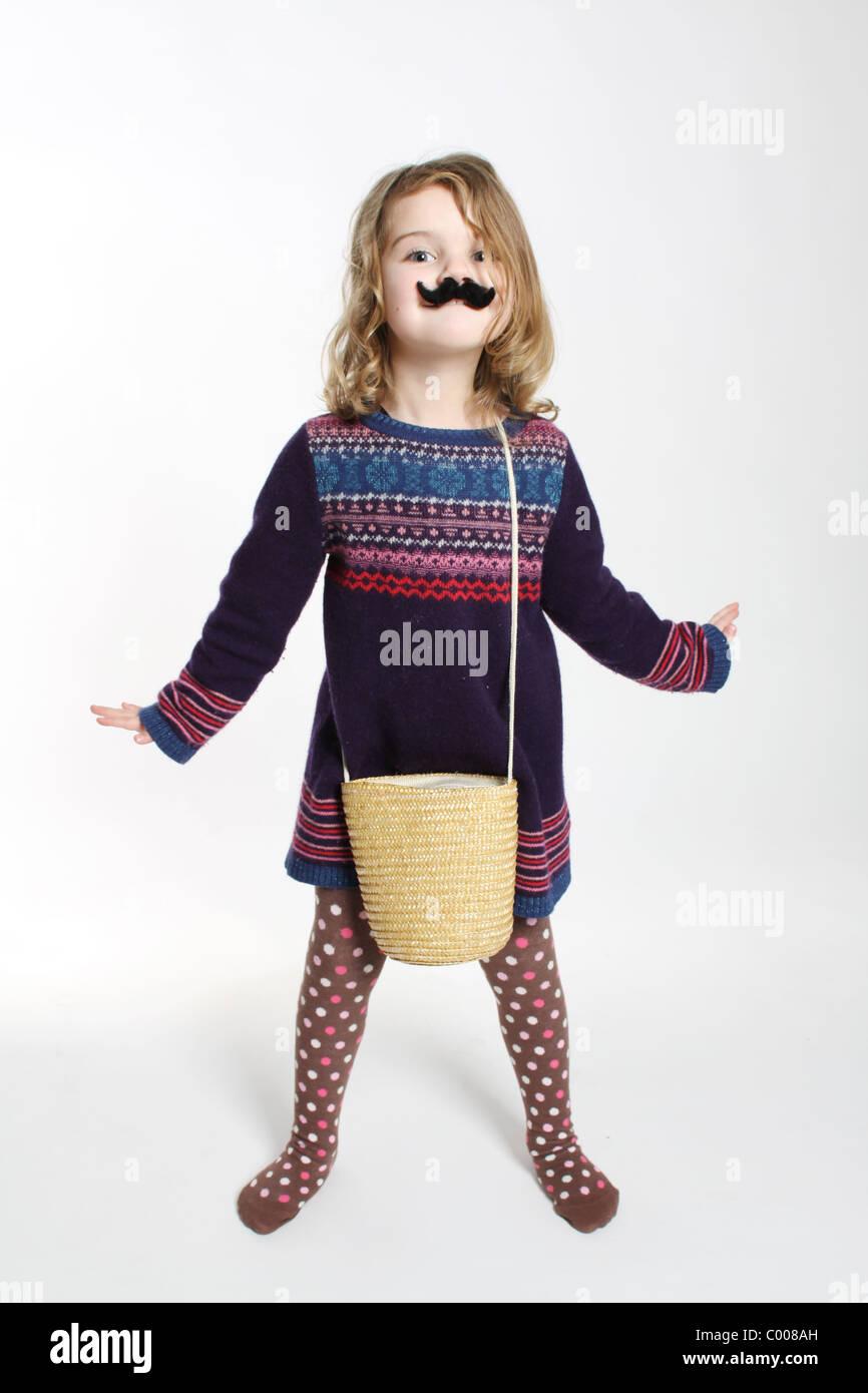 Una piena lunghezza shot di un po' di bianco ragazza caucasica guardando la fotocamera con un falso baffi neri, Immagini Stock