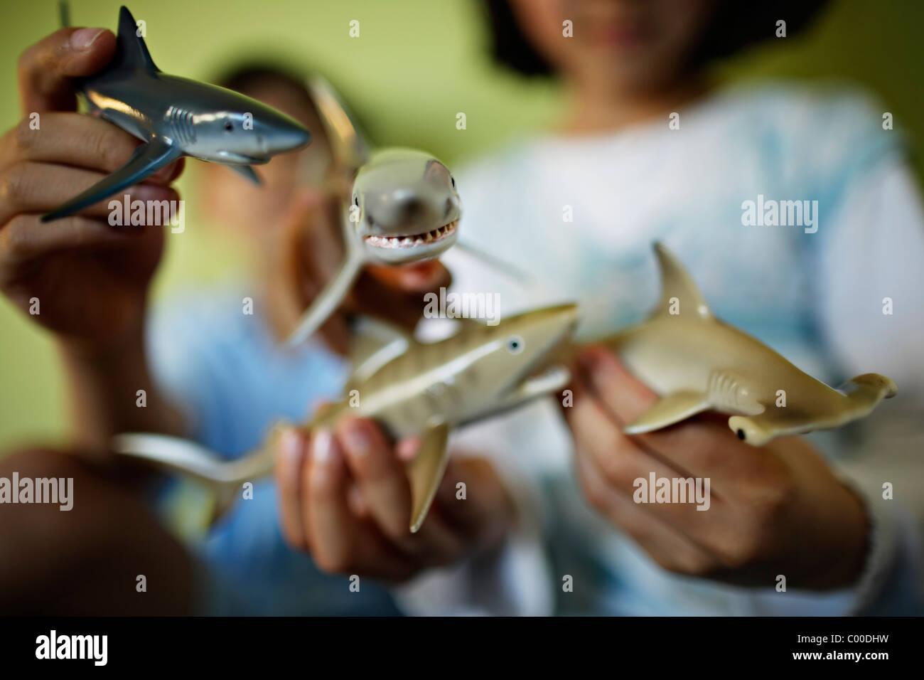 I bambini tenere squali giocattolo Immagini Stock