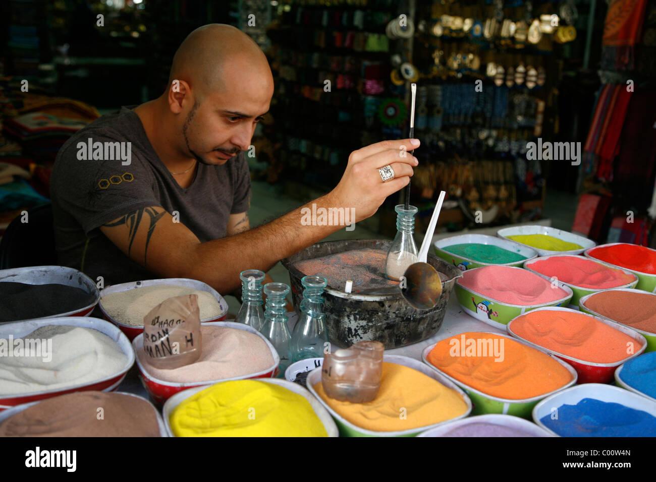 Un artista souvenir di riempimento delle bottiglie con la sabbia del deserto, Amman, Giordania. Immagini Stock