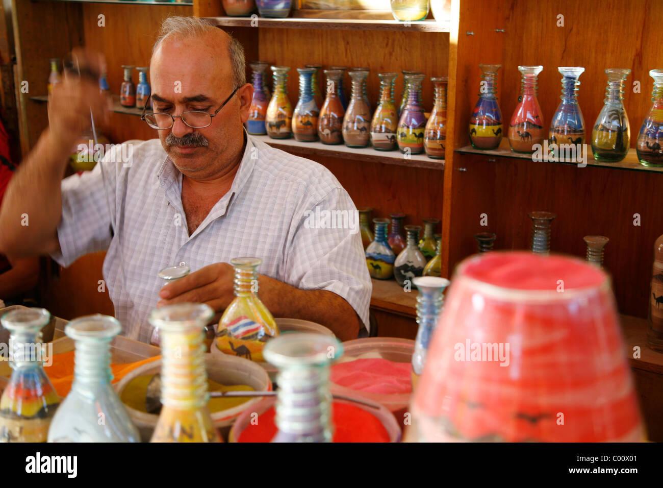 Un artista souvenir di riempimento delle bottiglie con la sabbia del deserto, Jerash, Giordania. Immagini Stock