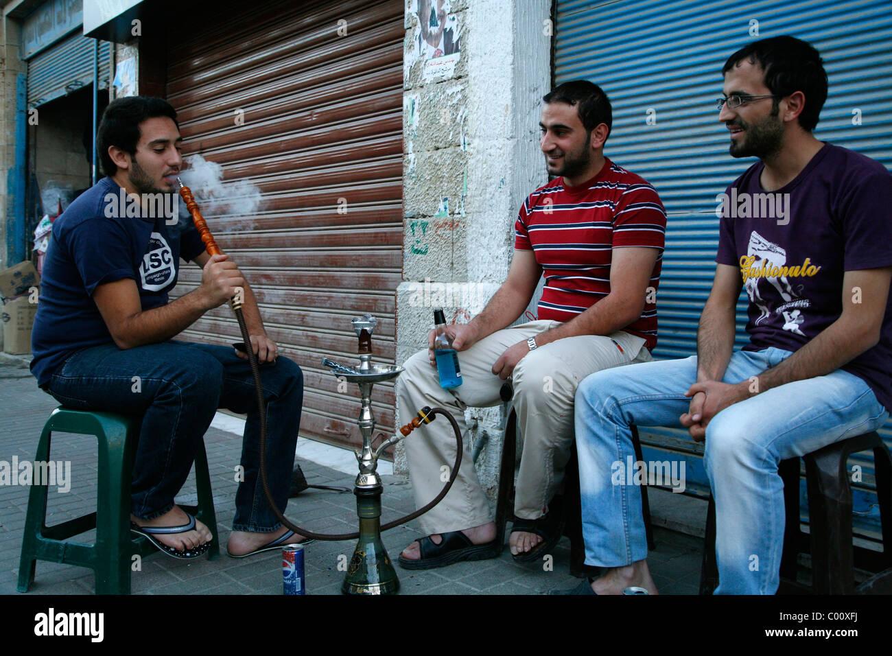 Giovani uomini fumatori nargileh (tubo d'acqua) su una strada di Madaba, Giordania. Immagini Stock