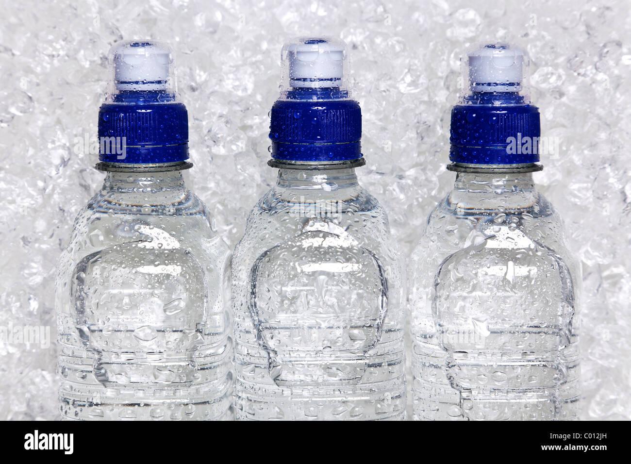 Foto di acqua minerale fredda in bottiglie di plastica sul ghiaccio tritato Immagini Stock