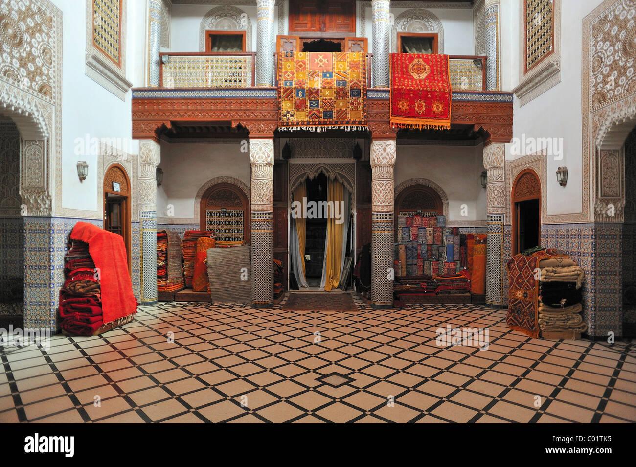 I tappeti di un tappeto concessionario, esposte per la vendita in un vecchio Riyadh Palace courtyard, Marrakech, Immagini Stock