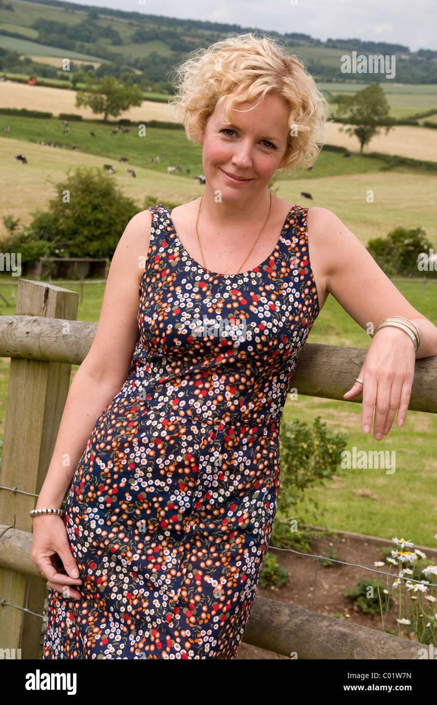 918a576ac8a1 Ritratto di una donna che indossa un vestito estivo appoggiata contro un  recinto circondato da campi e terreni agricoli