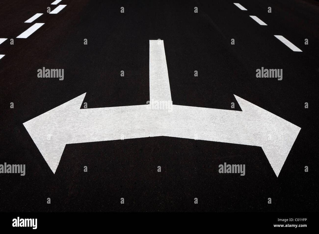 A sinistra e a destra frecce dipinte su asfalto stradale. Concetto di tornitura, decisione, scelta, in che modo, Immagini Stock