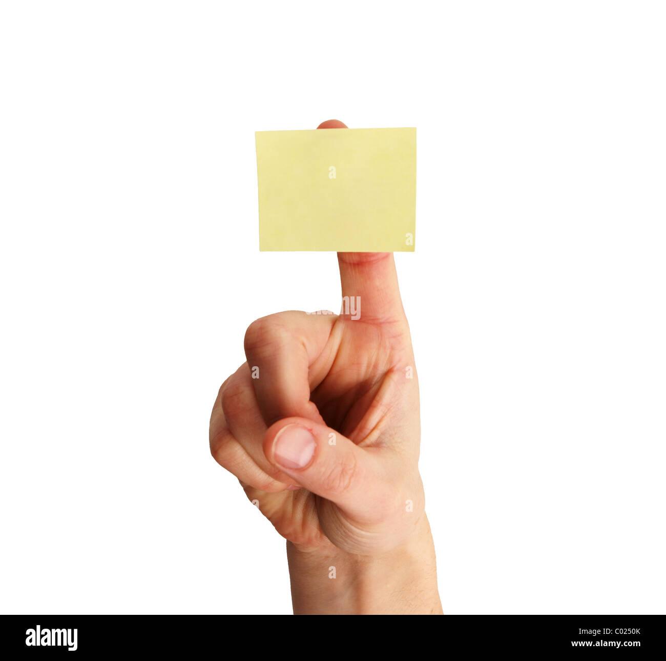 Blank bigliettino giallo su una donna di dito isolati su sfondo bianco Immagini Stock