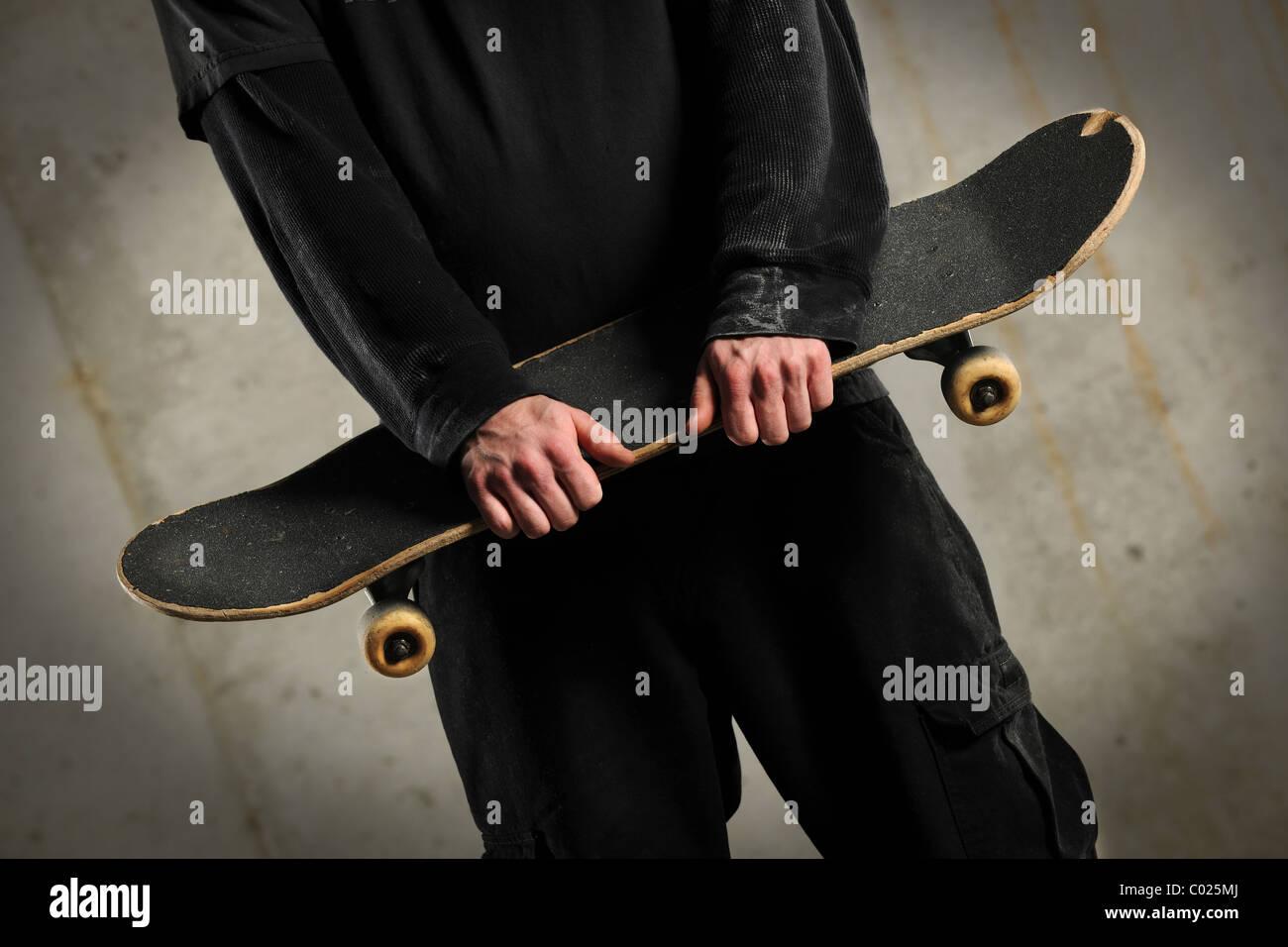 La sezione centrale dell'uomo azienda skateboard su sfondo di calcestruzzo con spotlight Immagini Stock