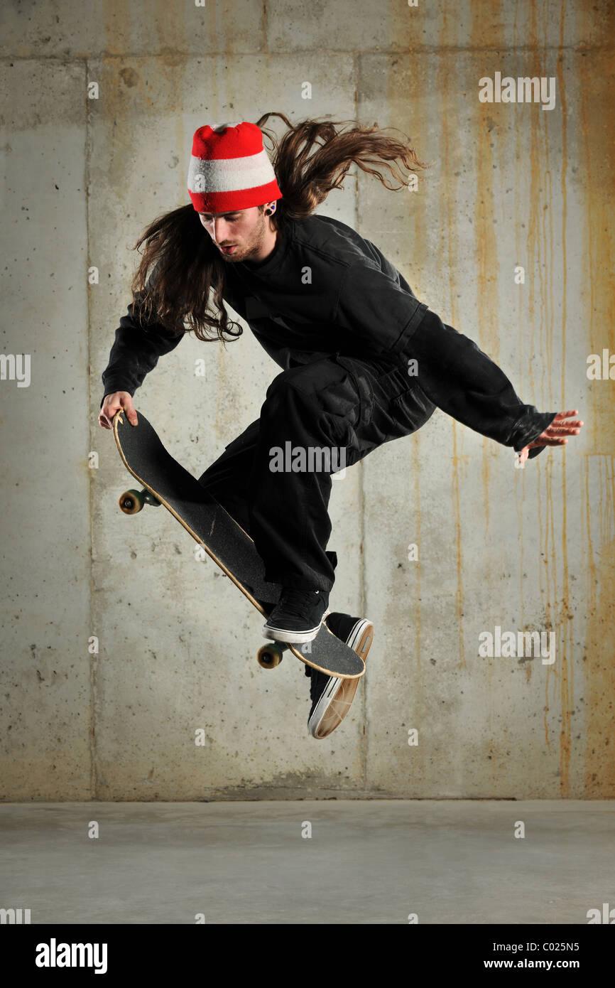 Guidatore di skateboard esecuzione di saltare su edificio grunge Immagini Stock
