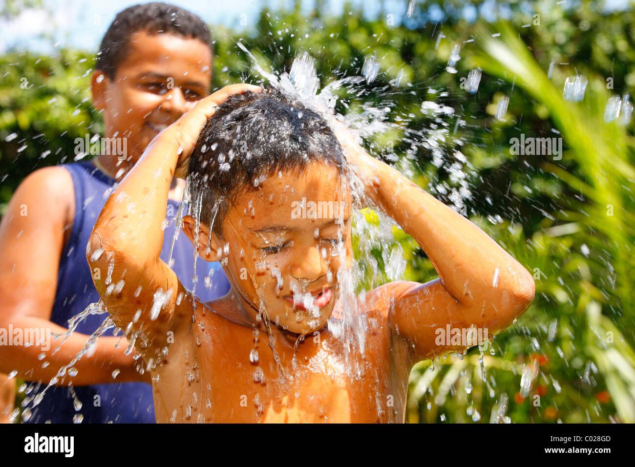 Ragazzo che viene spruzzato con un tubo flessibile di acqua, Fortaleza Ceará, Brasile, Sud America Immagini Stock