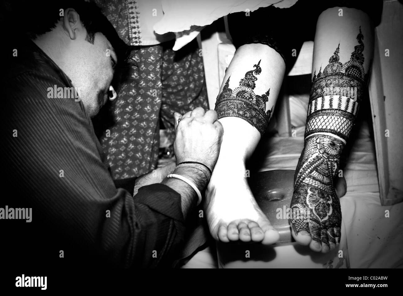 Un indiano sposa ottiene il suo caviglie dipinta con henna a Nuova Delhi in India. Immagini Stock