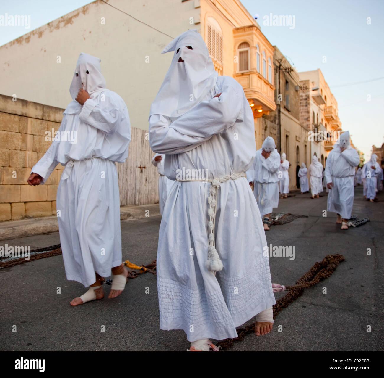 La penitenza portatori trascina le catene pesanti durante la sfilata del Venerdì Santo svoltasi in varie città Immagini Stock