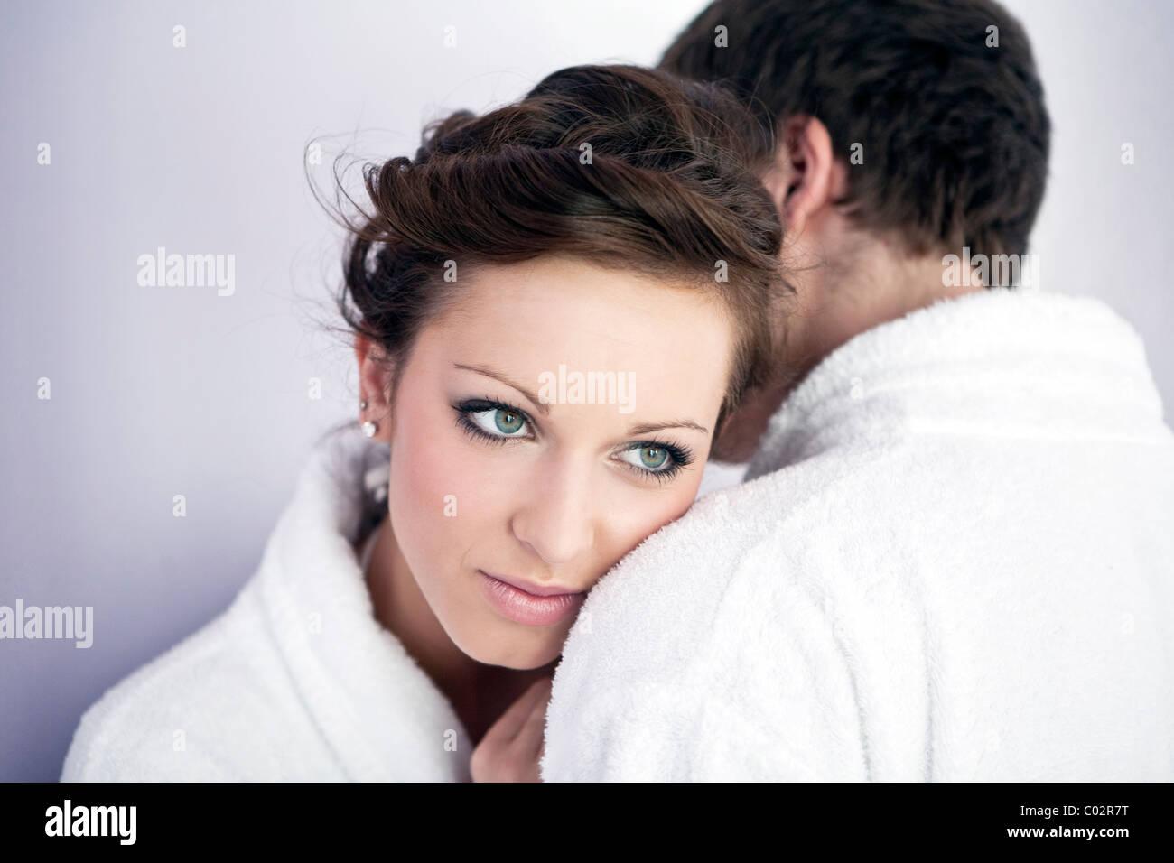 Giovane donna e giovane uomo in accappatoio, abbraccio Immagini Stock