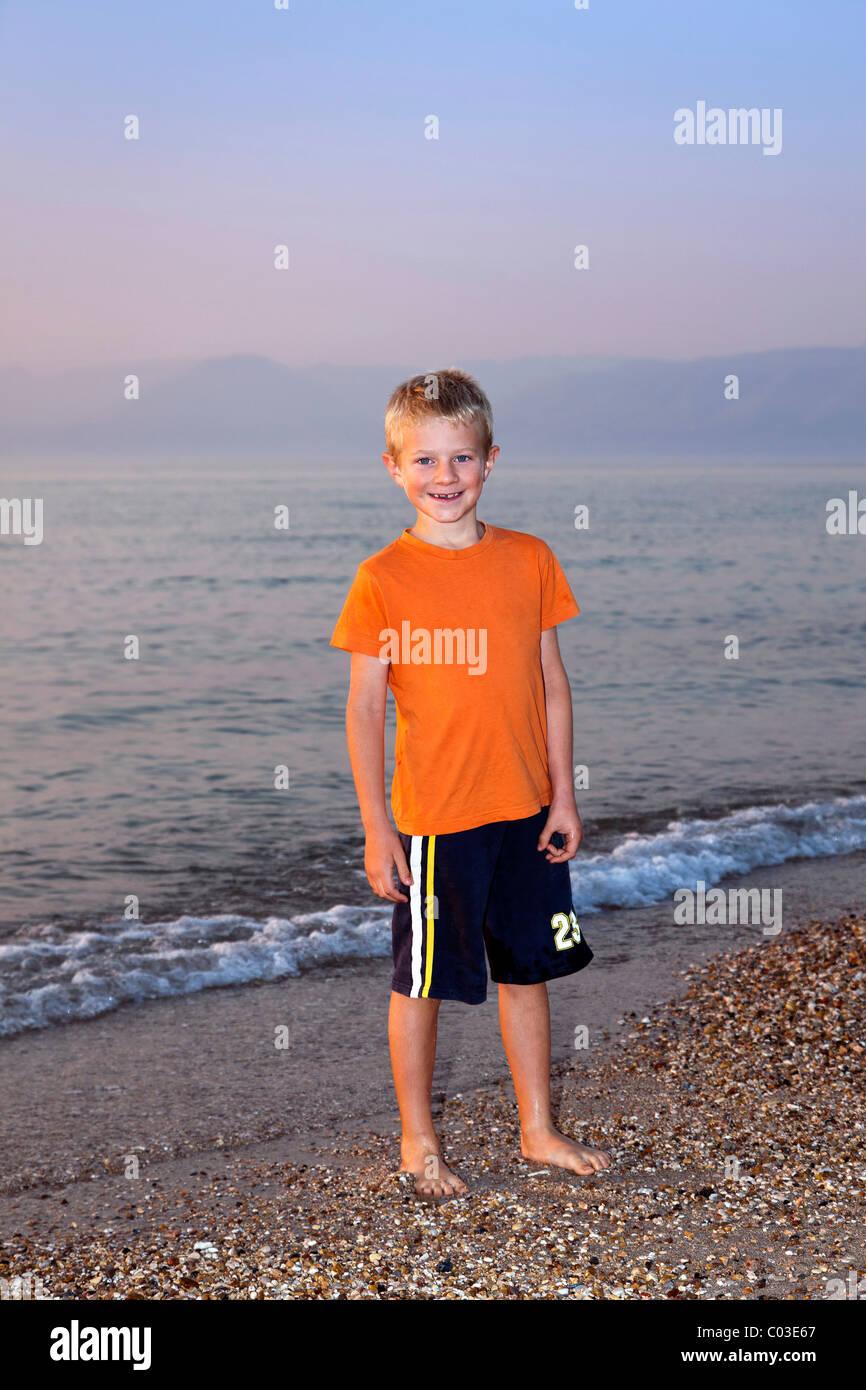 Ragazzo, 7, di sera su una spiaggia di ciottoli, Corfu, Isole Ionie, Grecia, Europa meridionale, Europa Immagini Stock