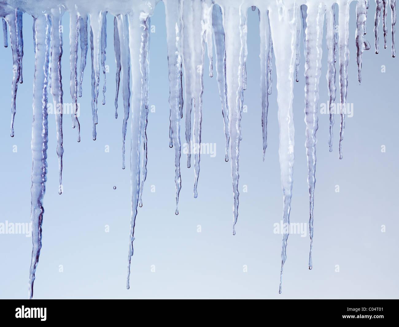 Ghiaccioli di fusione isolati su fondo azzurro Immagini Stock