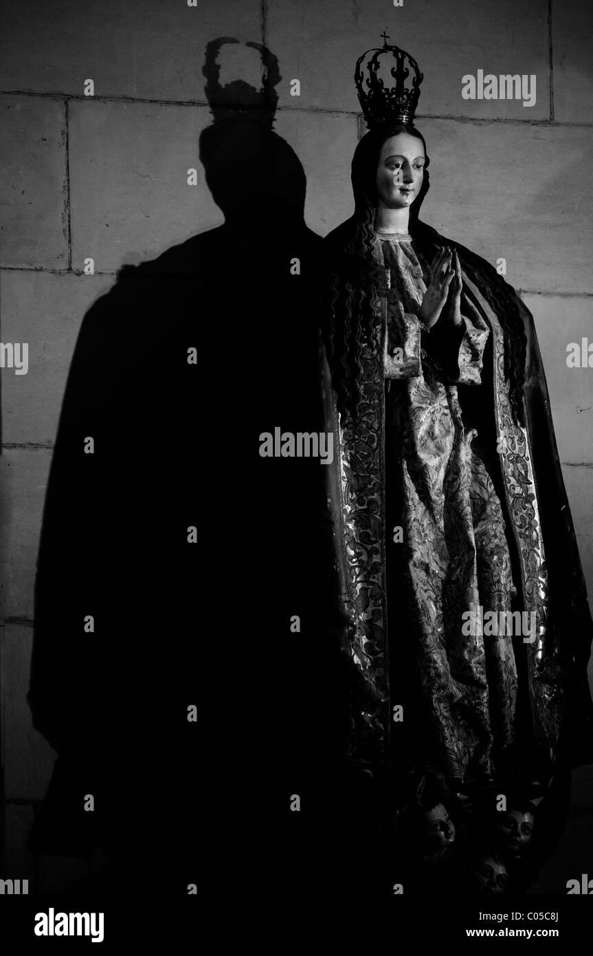La statua della Vergine Maria che gettano ombre su una parete Immagini Stock