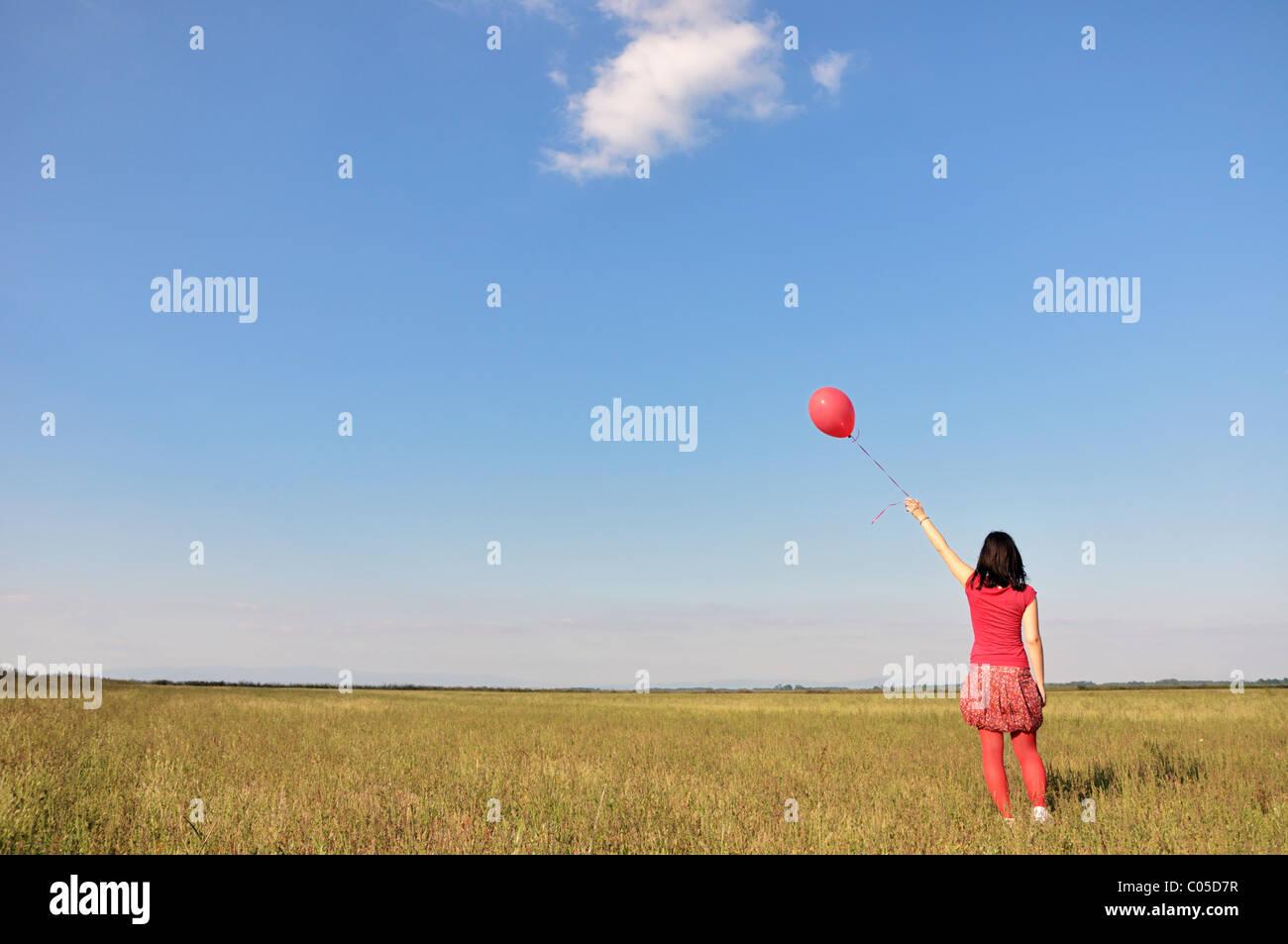 Felice giovane donna azienda palloncino rosso Immagini Stock