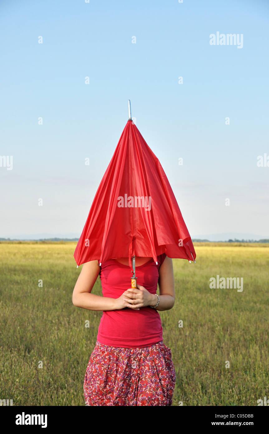 Giovane donna azienda Ombrellone rosso Immagini Stock