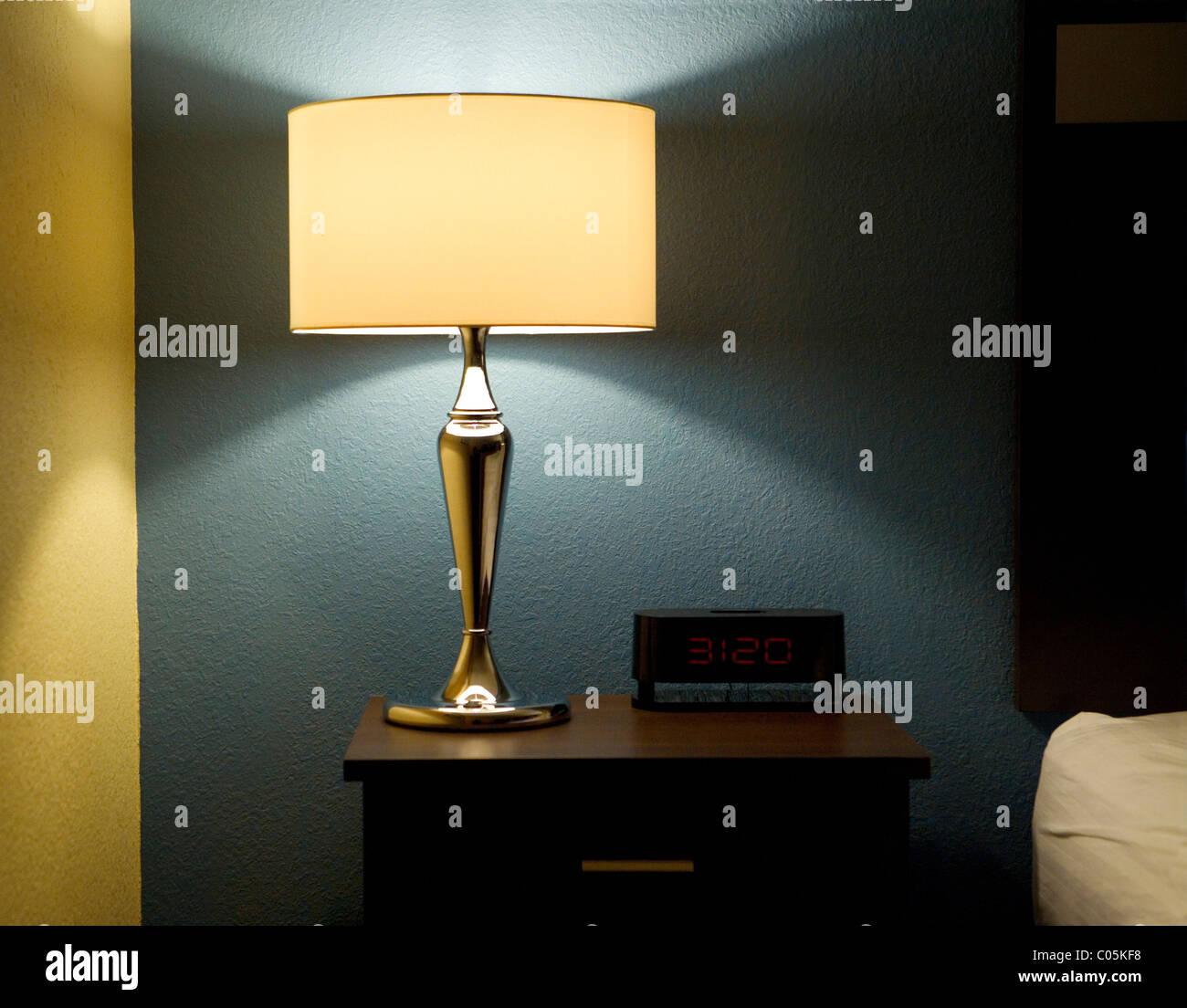 Lampada, orologio digitale e fine tabella accanto a un letto. Immagini Stock