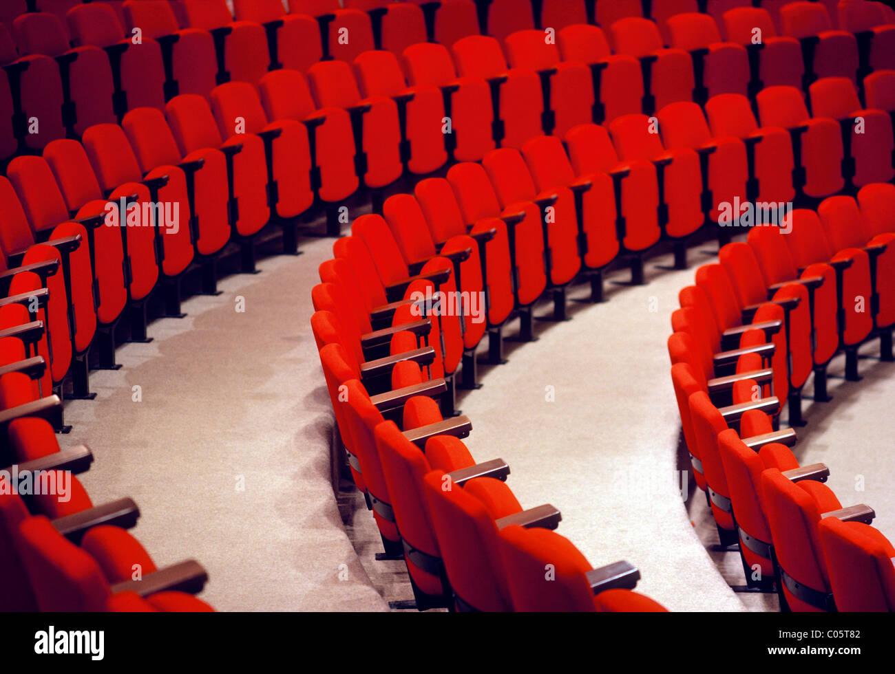 Righe curve di rosso posti in un auditorium. Immagini Stock