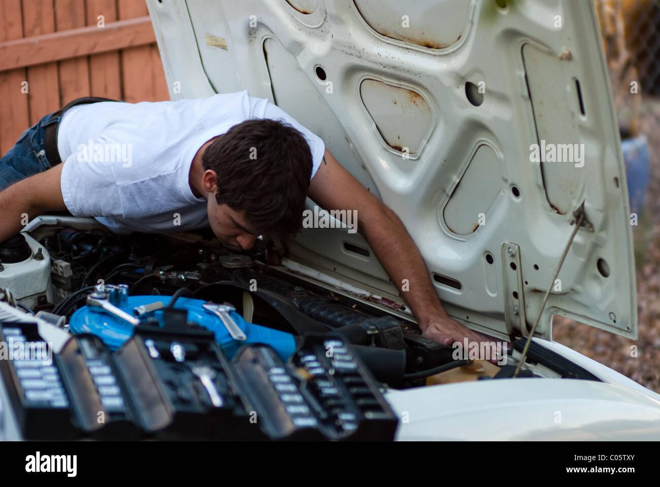 Uomo al lavoro su auto nel cortile. Do it yourself meccanico di eseguire la riparazione auto. Esaminando il vano Immagini Stock