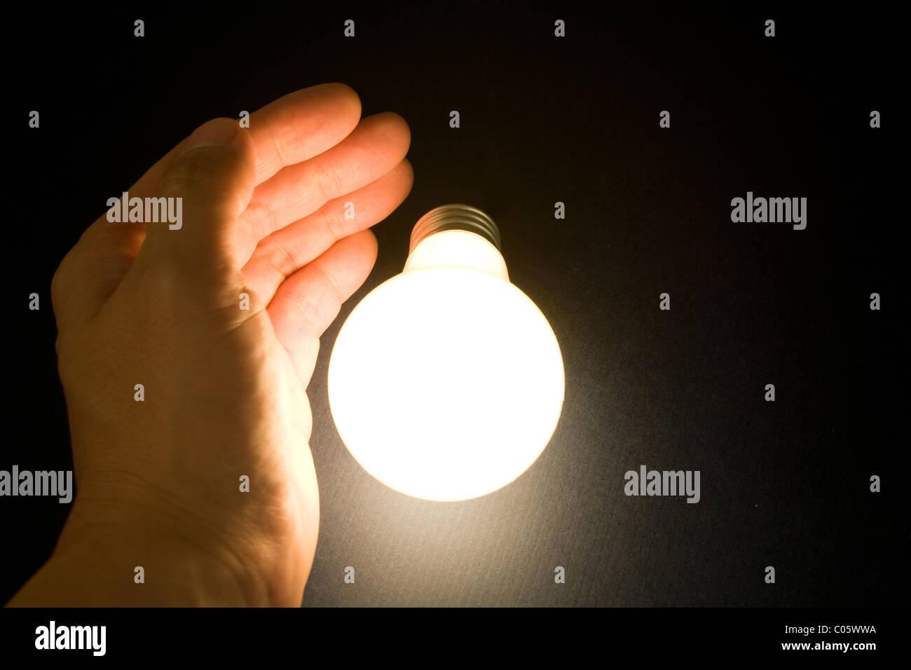 Mano e una luce brillante lampadina, concetto di ispirazione e idee Immagini Stock