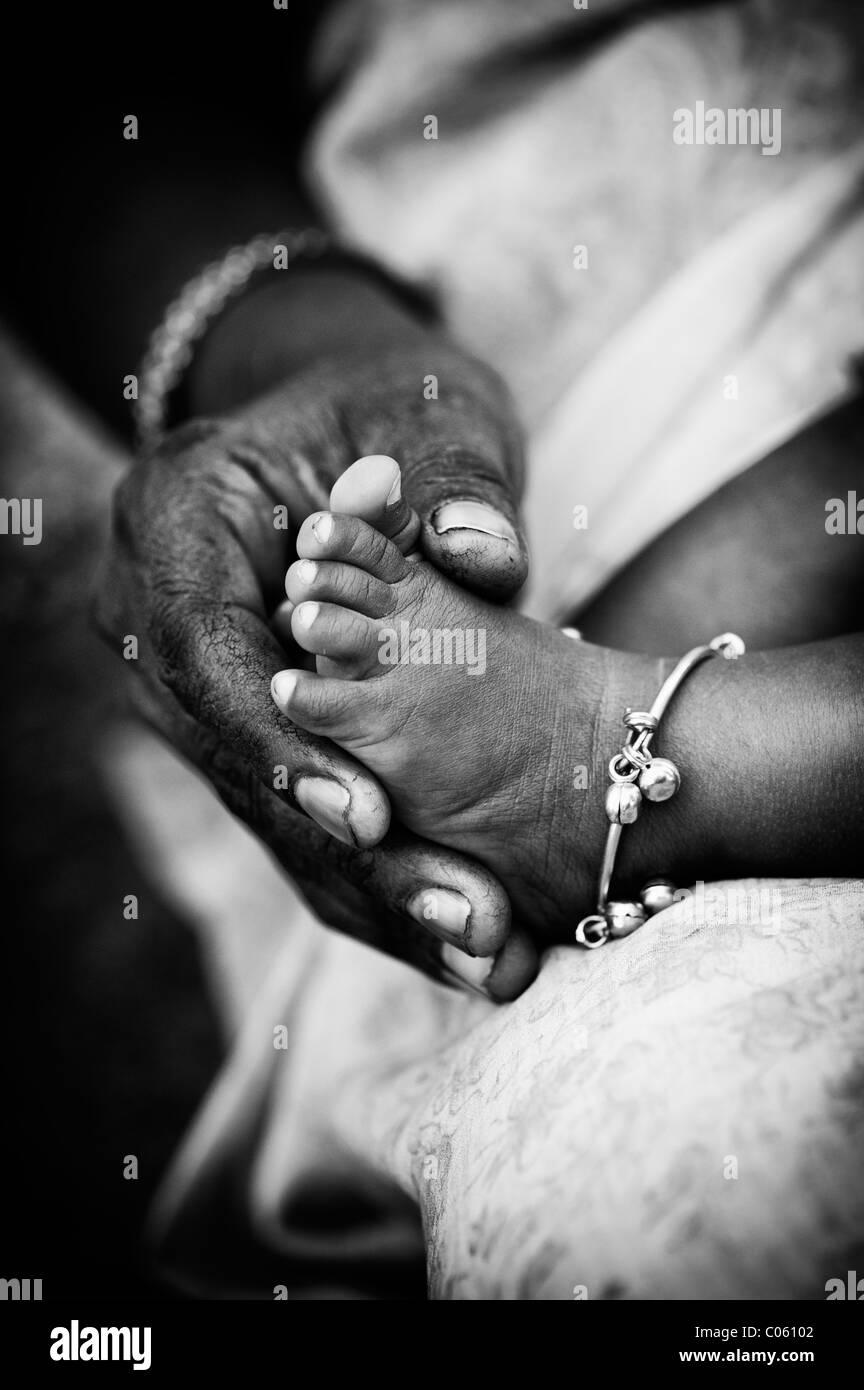 Madre indiana tenendo i bambini a piedi nudi. Monocromatico. Andhra Pradesh, India Immagini Stock