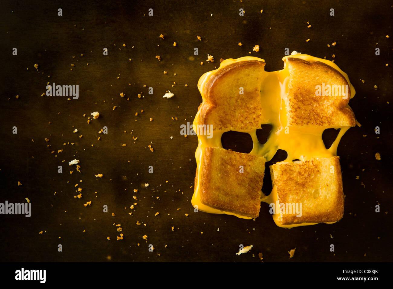 Un formaggio alla griglia panino tagliato in quattro piazze tirando il formaggio su una tavola di legno Foto Stock