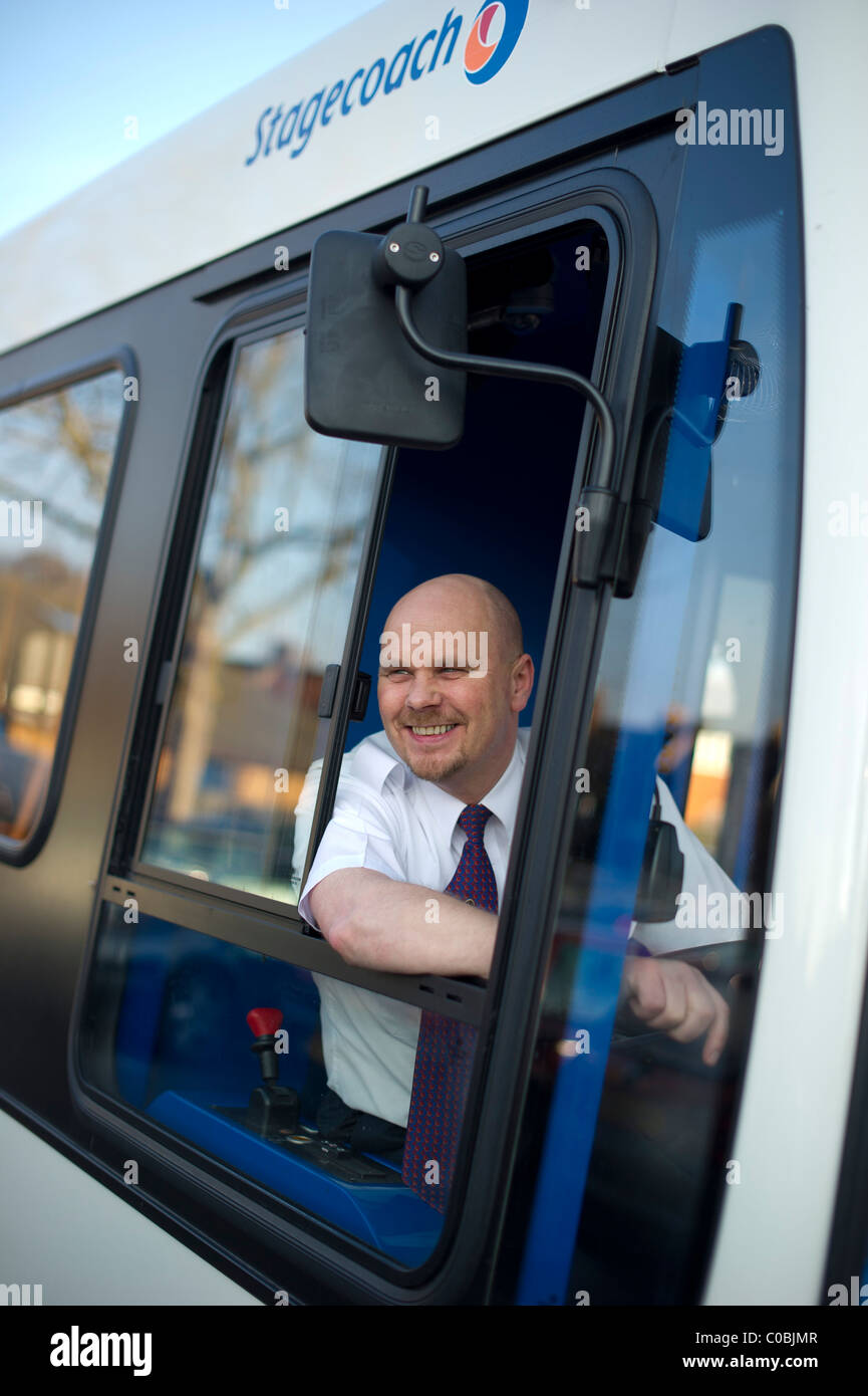 Un felice conducente di bus con la sua testa guardando fuori di un bus Immagini Stock