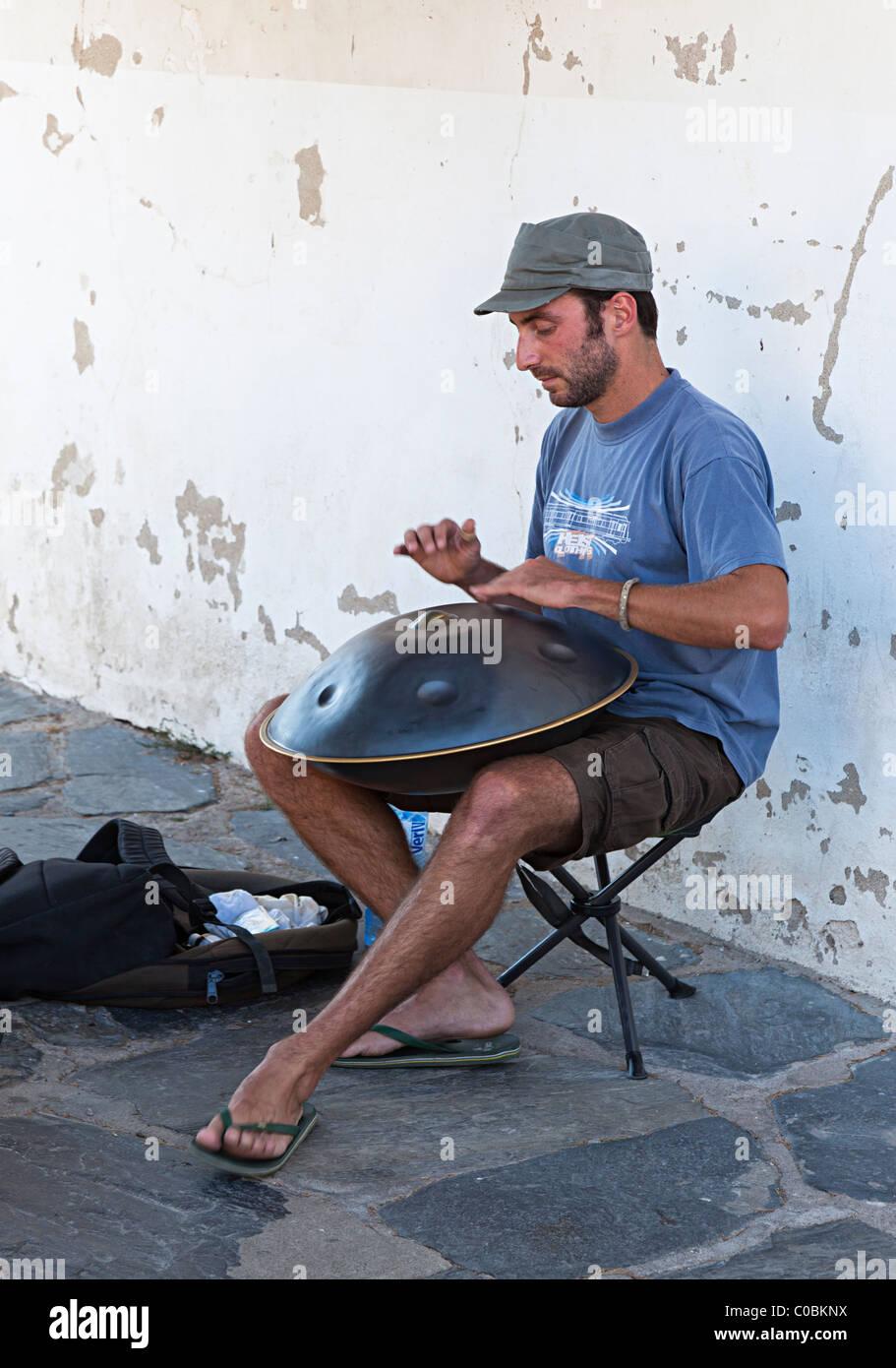 L'uomo gioca un appendere lo strumento musicale per i suggerimenti nella cittadina balneare di Cadaqués Immagini Stock