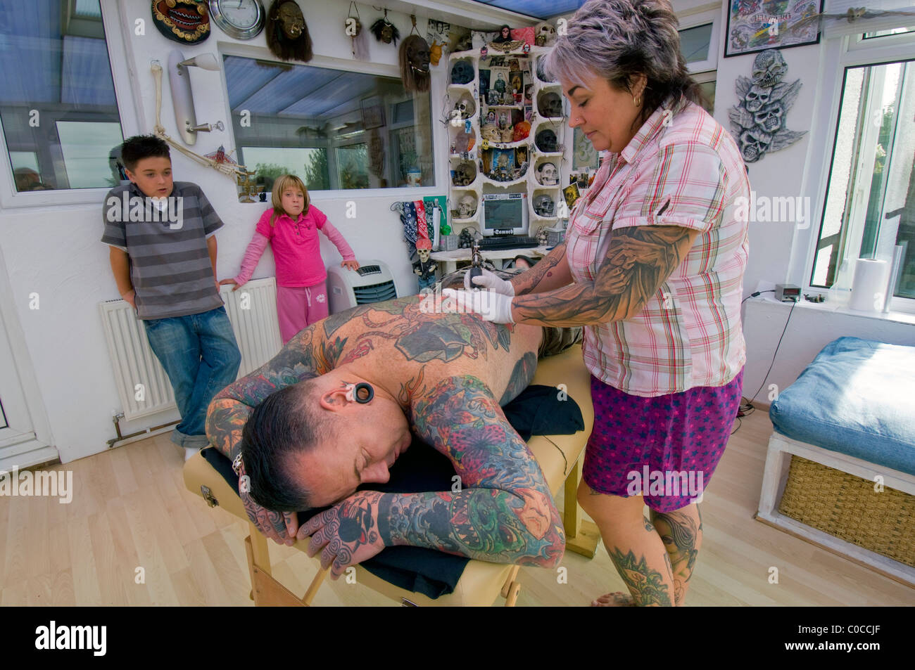 Una donna tattooist funziona su un disegno sul suo marito torna, guardati da loro due bambini annoiati. Immagini Stock