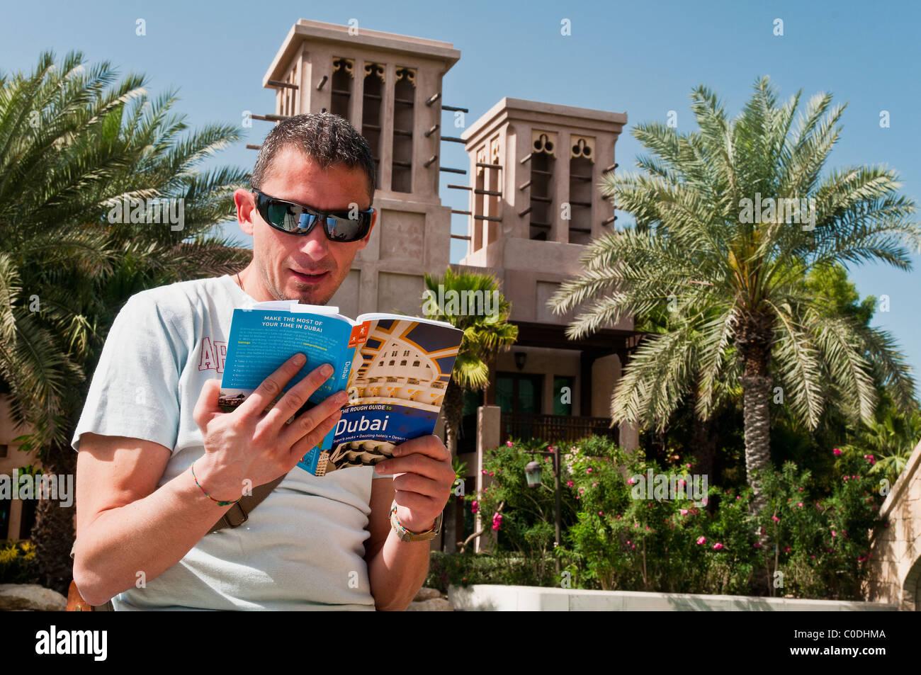 Uomo turistica la lettura di una guida turistica di Dubai a Madinat Jumeirah con torri del vento in background, Immagini Stock