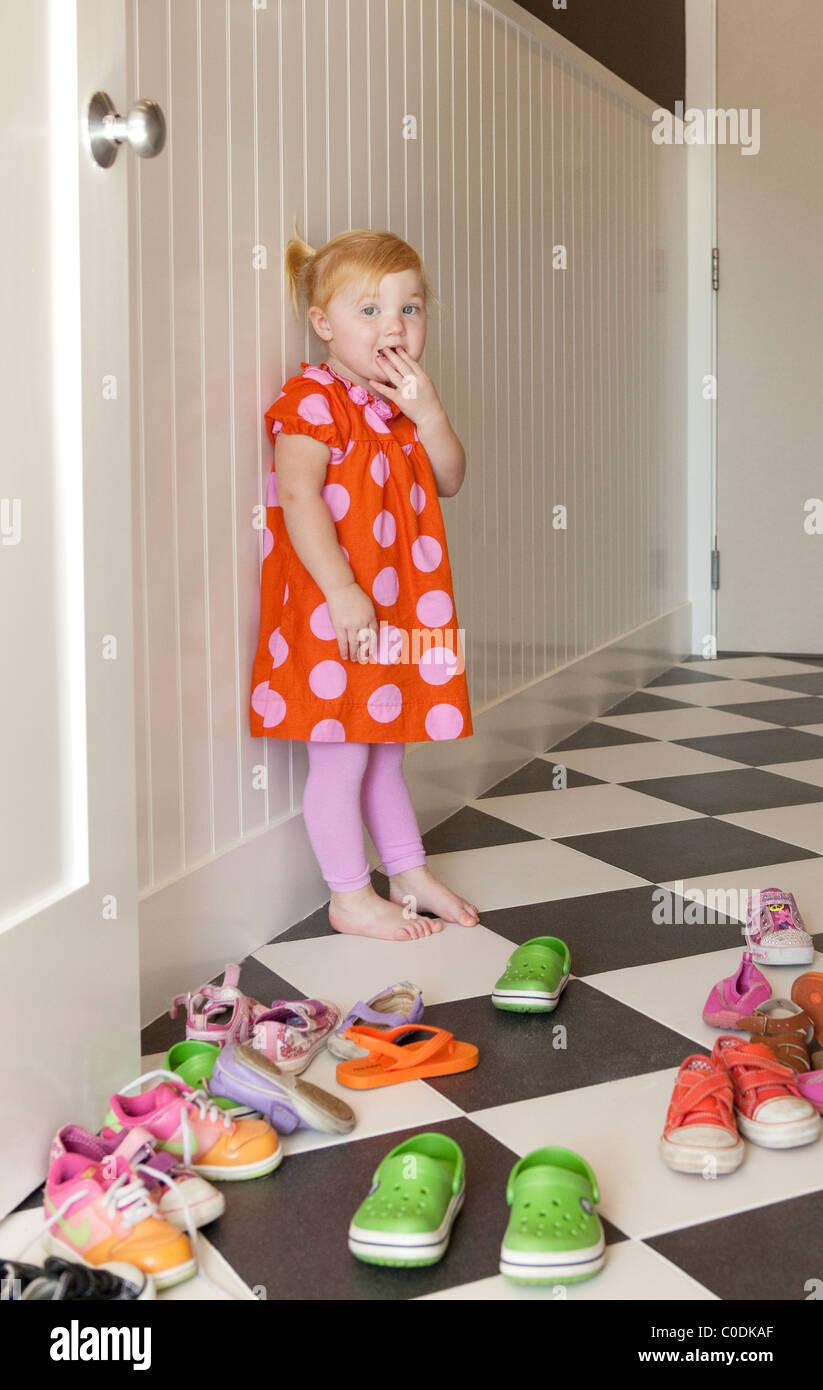 Bambina di decidere quali scarpe da indossare Immagini Stock