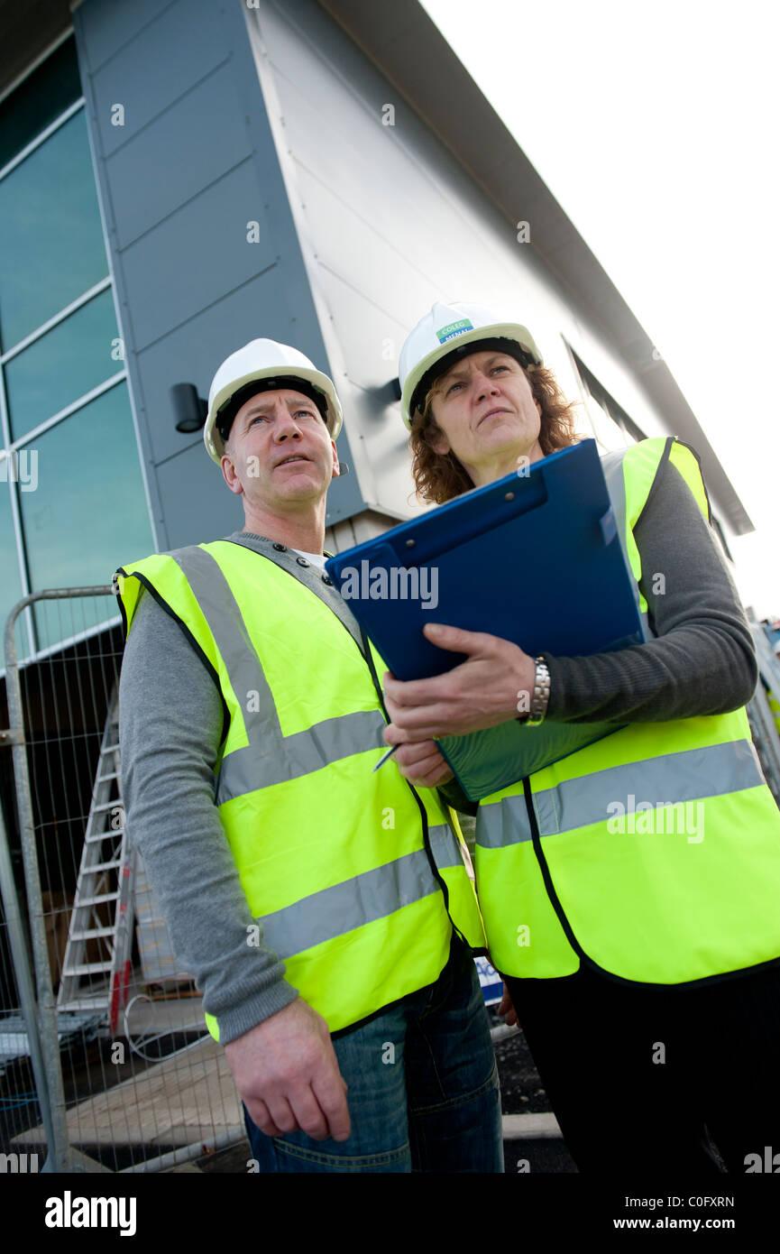 Due persone [uomo donna femmina maschio] facendo una salute e sicurezza relazione di ispezione su un sito di costruzione Immagini Stock