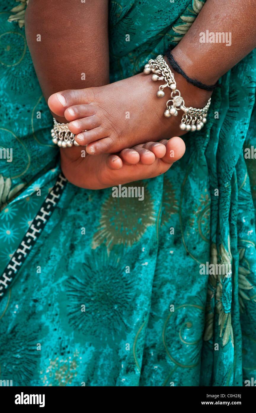 Bambini indiani a piedi nudi contro le madri floreale verde sari. Andhra Pradesh, India Immagini Stock