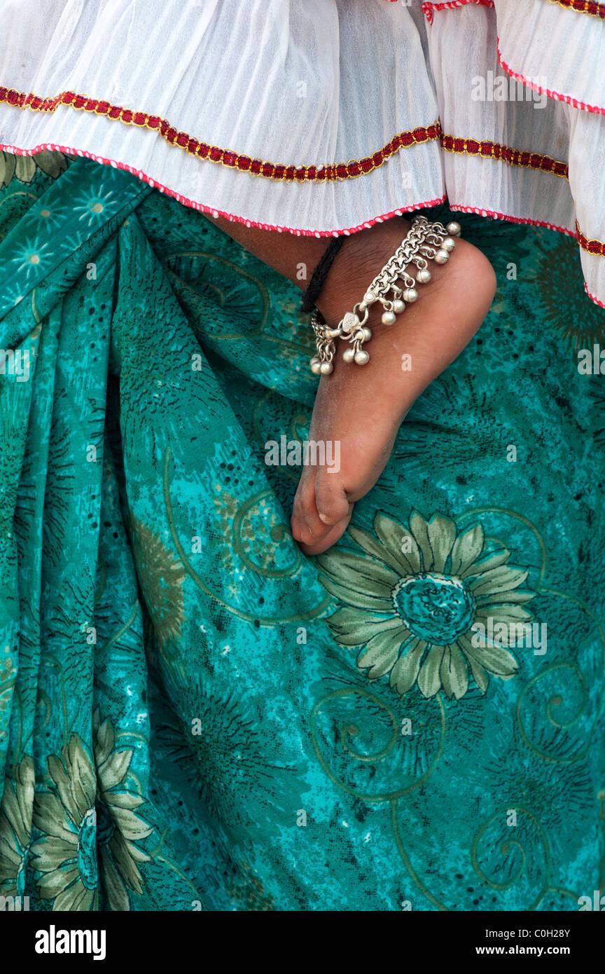 Bambini indiani piedi nudi contro le madri floreale verde sari. Andhra Pradesh, India Immagini Stock