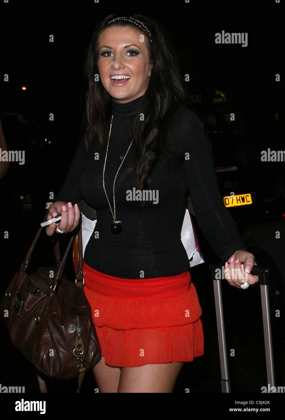 Amy Alexandra a piedi attraverso Mayfair indossando un rosso mini gonna e  portante un matching valigia 67169e26b97