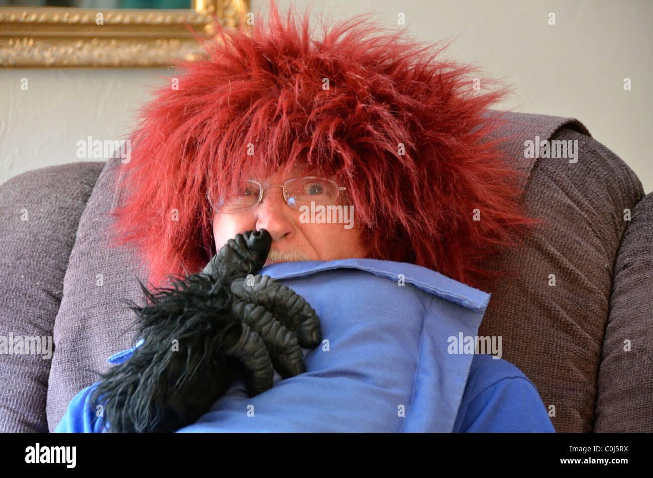 Un uomo anziano agisce silly mettendo su una rossa parrucca fuzzy. Stati Uniti d'America. Foto Stock